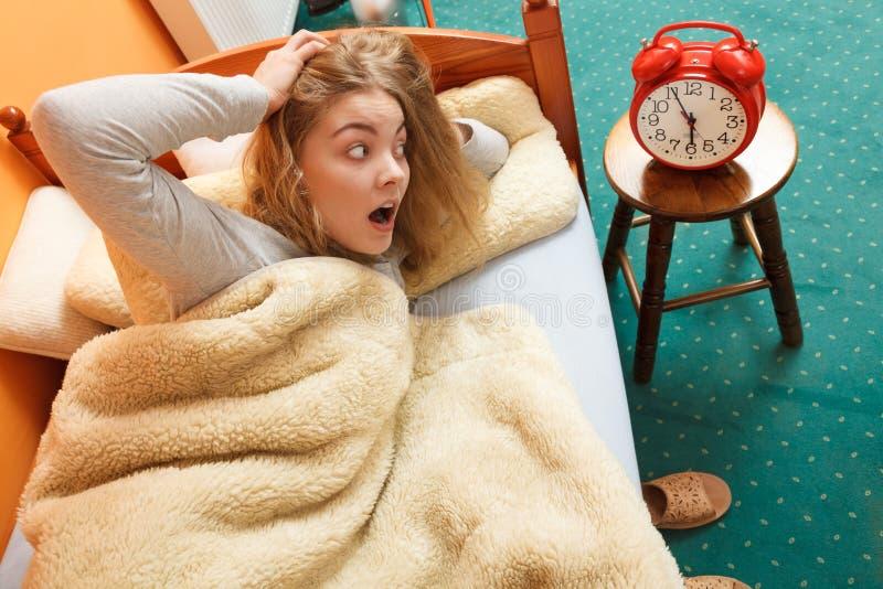 Mujer que despierta tarde apagando el despertador imágenes de archivo libres de regalías