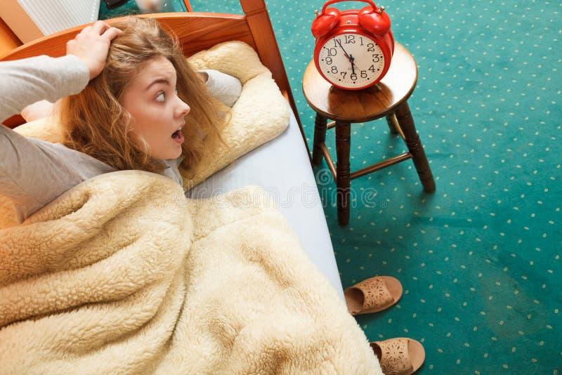 Mujer que despierta tarde apagando el despertador fotos de archivo