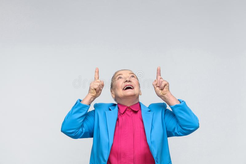 Mujer que destaca el finger en el espacio de la copia y la sonrisa dentuda imagen de archivo libre de regalías
