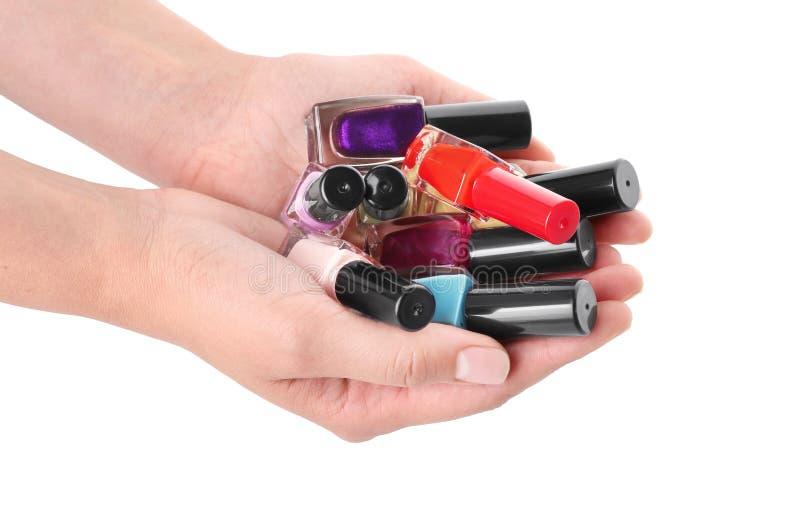 Mujer que detiene las botellas de esmaltes de uñas coloridos en el fondo blanco fotos de archivo libres de regalías