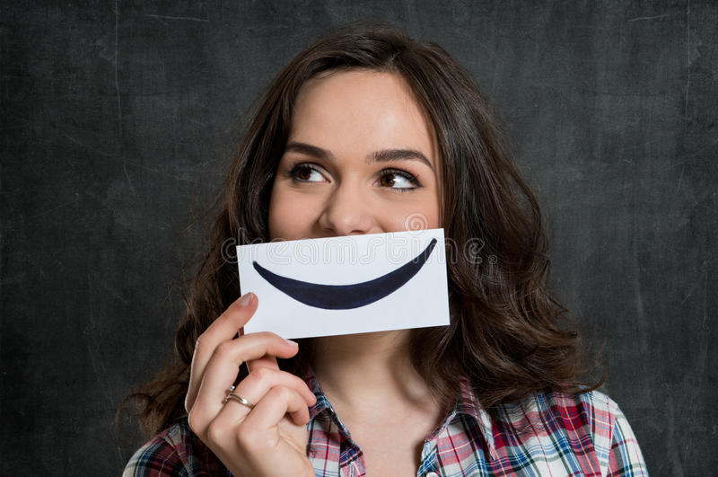 Mujer que detiene a Smiley Emoticon imagen de archivo libre de regalías