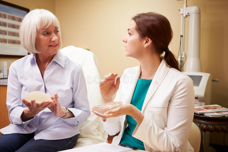 Mujer que discute el aumento del pecho con el cirujano plástico foto de archivo