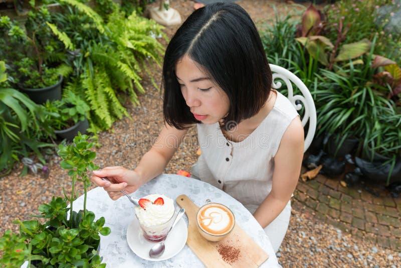 Mujer que disfruta de la bagatela del café y de la fresa imagen de archivo