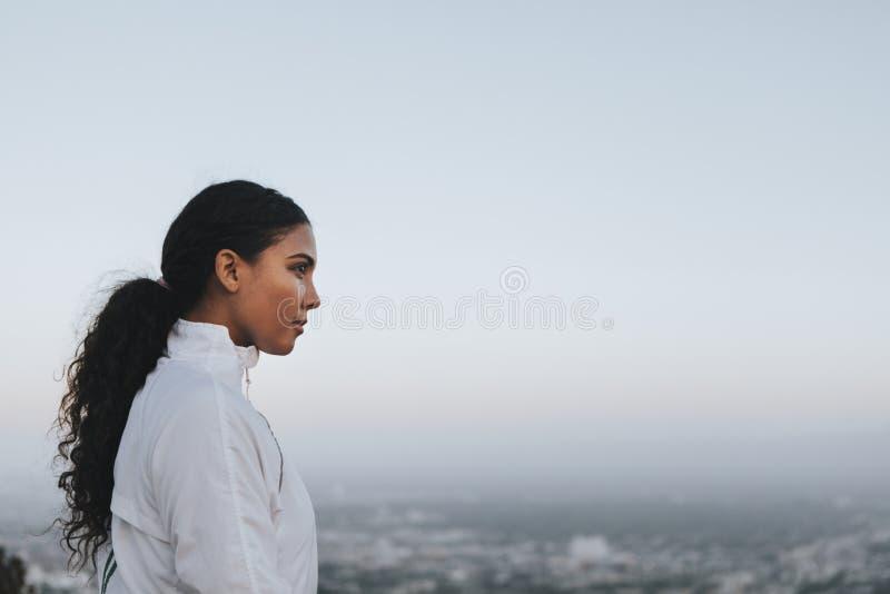 Mujer que disfruta de la opinión de la ciudad de una colina imágenes de archivo libres de regalías