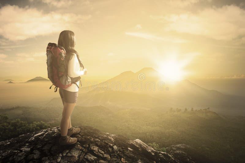 Mujer que disfruta de la opinión del valle de la ladera imagen de archivo libre de regalías