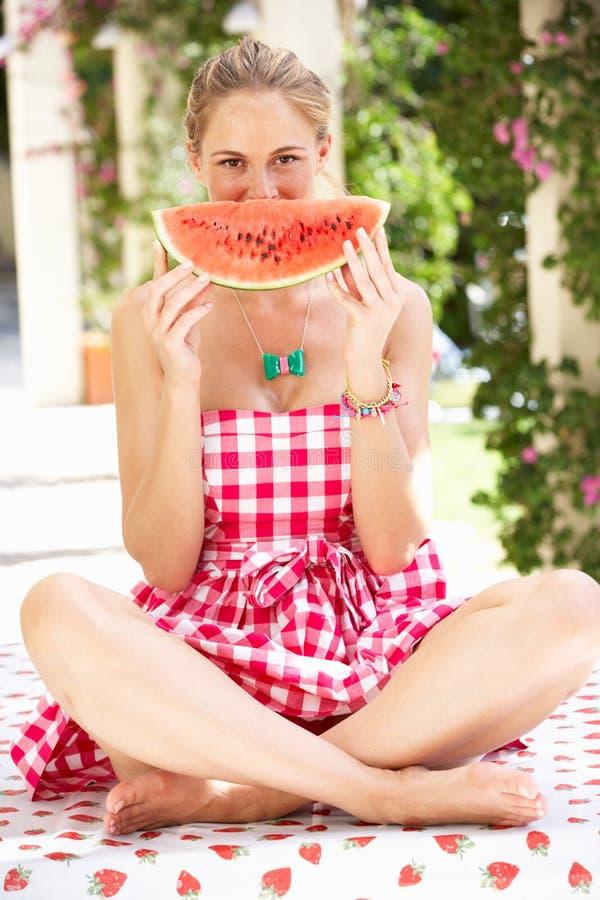 Mujer que disfruta de la rebanada de melón de agua imágenes de archivo libres de regalías