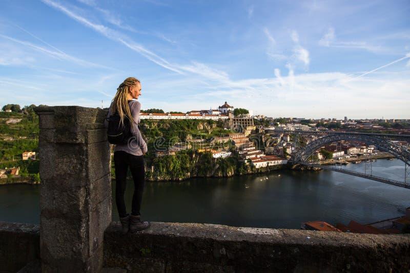Mujer que disfruta de la vista del río del Duero y del puente de Dom Luis I en Oporto imagenes de archivo
