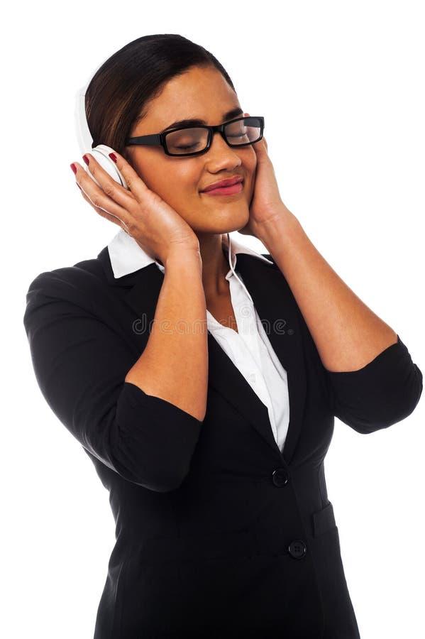 Mujer Que Disfruta De Música A Través De Los Auriculares Foto de archivo