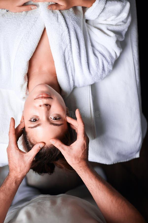 Mujer que disfruta de masaje facial antienvejecedor Foto al revés de la mujer relajante imagenes de archivo