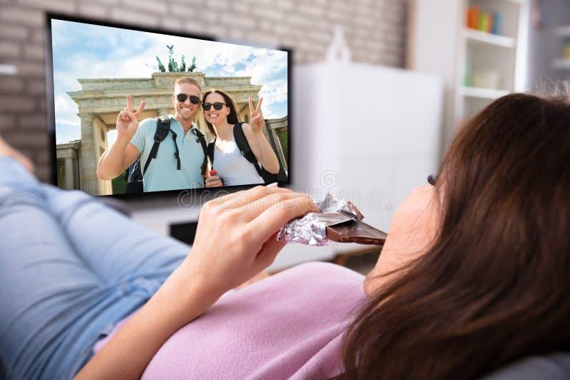 Mujer que disfruta de pel?cula en la televisi?n foto de archivo