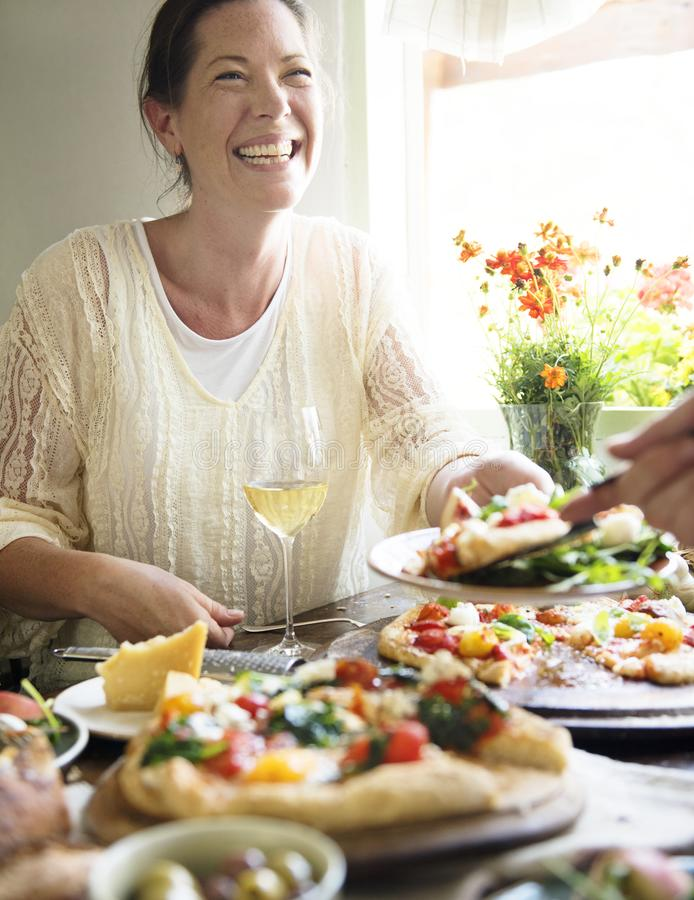 Mujer que disfruta de una cena de la pizza foto de archivo