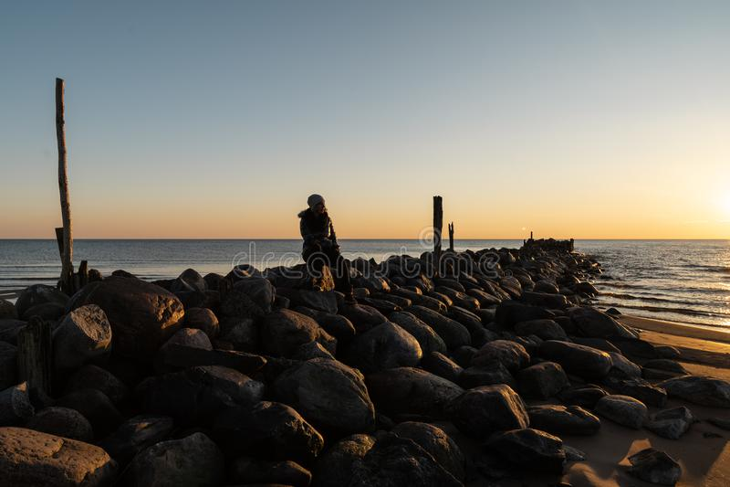 Mujer que disfruta de una puesta del sol fría de la primavera en una playa del canto rodado cerca del mar Báltico imágenes de archivo libres de regalías