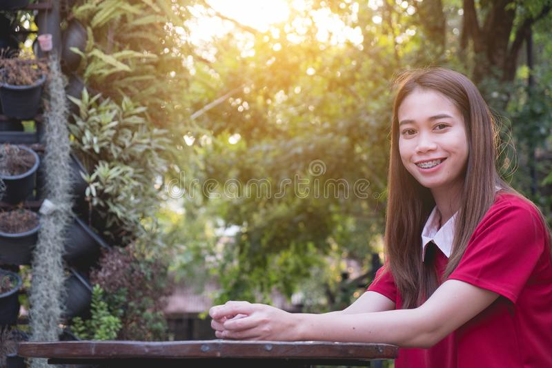 Mujer que disfruta del ajuste hermoso de la puesta del sol en silla en el parque fotos de archivo libres de regalías