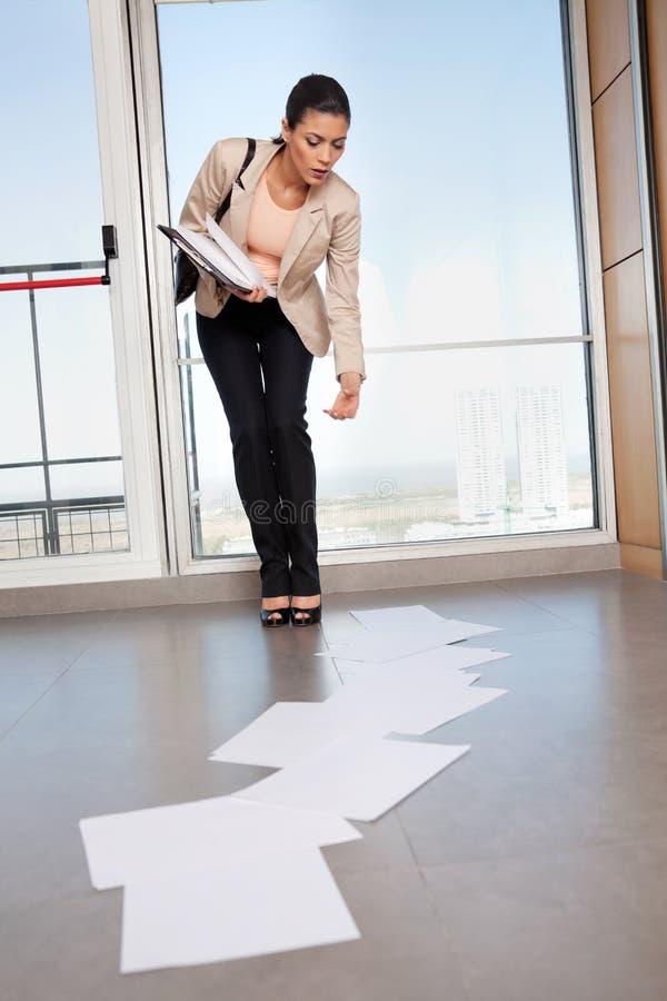 Mujer que dobla abajo para recoger los papeles en piso fotos de archivo