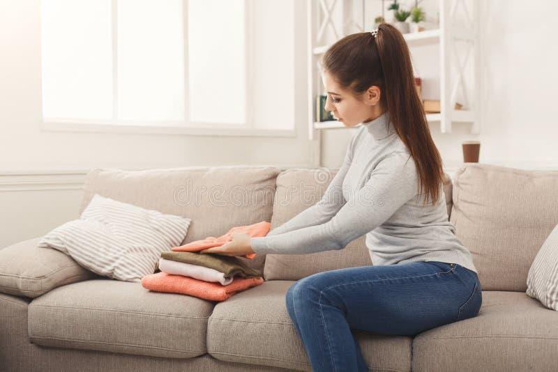 Mujer que dobla las camisetas limpias en casa fotografía de archivo libre de regalías
