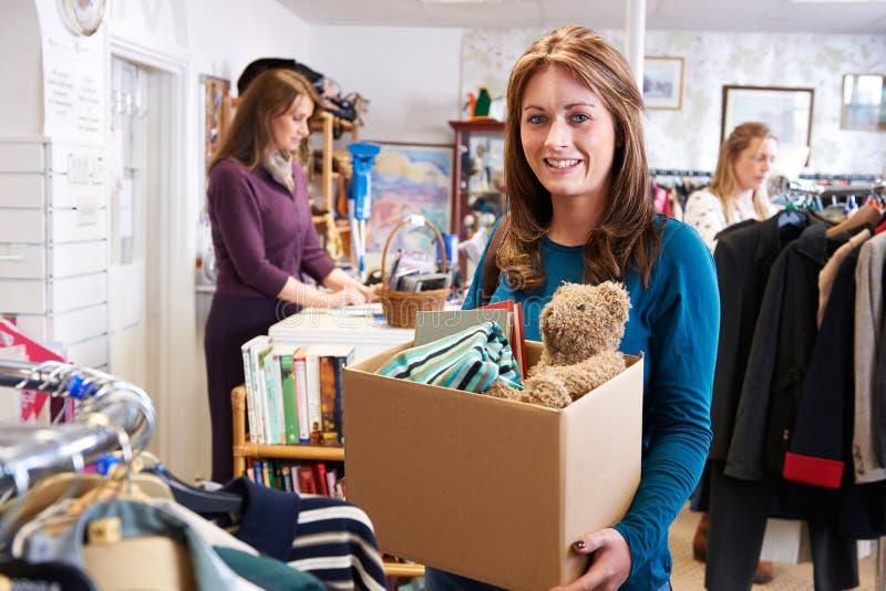Mujer que dona artículos indeseados a la tienda de la caridad foto de archivo libre de regalías
