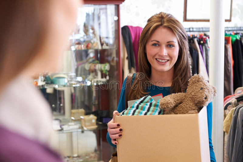 Mujer que dona artículos indeseados a la tienda de la caridad imagenes de archivo