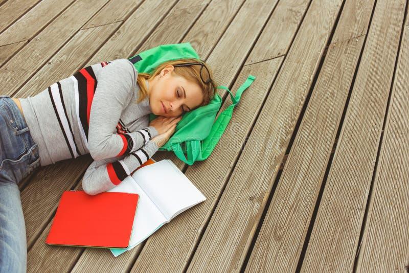 Mujer que duerme al lado del cuaderno abierto en superficie de madera imágenes de archivo libres de regalías