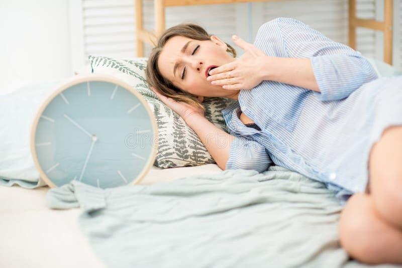 Mujer que duerme con el reloj en la cama imagenes de archivo