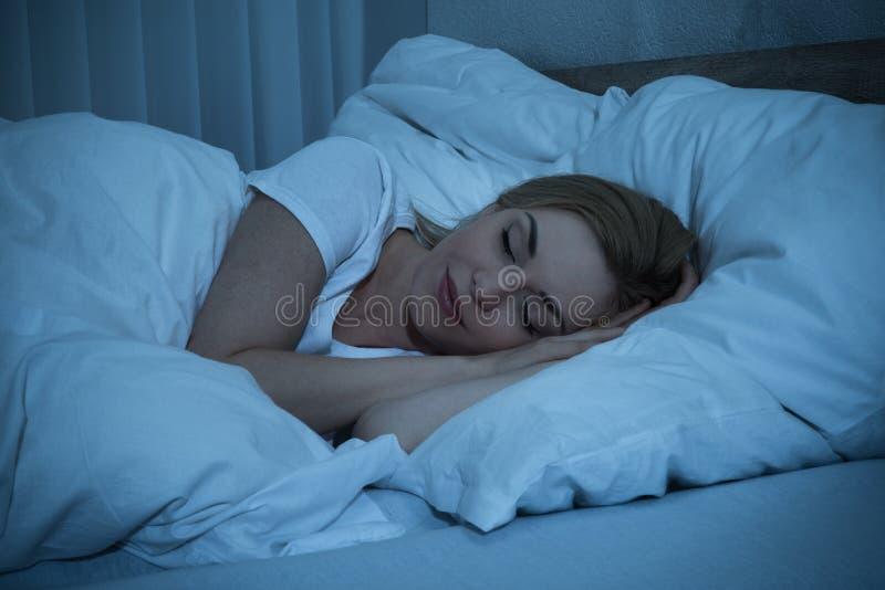 Mujer que duerme en cama fotos de archivo libres de regalías