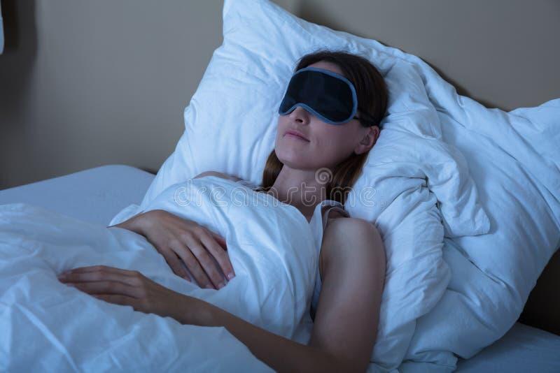 Mujer que duerme en cama con la máscara de ojo imagen de archivo