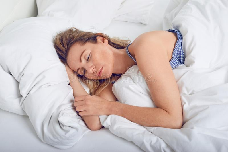 Mujer que duerme en cama debajo del edredón blanco foto de archivo