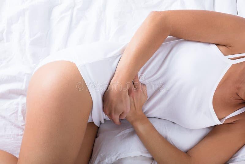 Mujer que duerme en la cama que tiene dolor de estómago foto de archivo