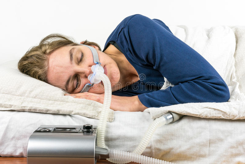 Mujer que duerme en su lado con la máquina de CPAP en el primero plano imagen de archivo