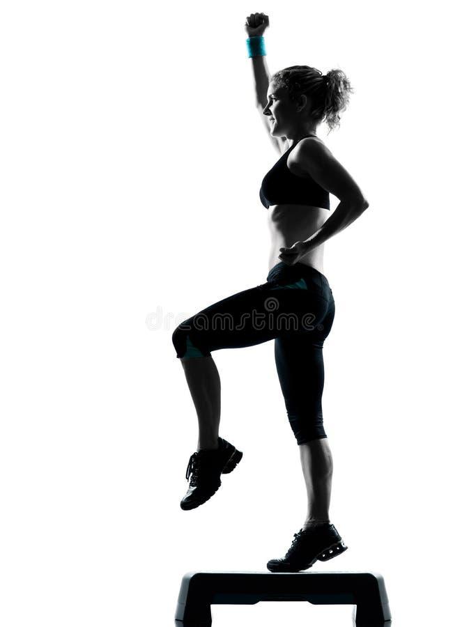Mujer que ejercita aeróbicos del paso de progresión imagenes de archivo