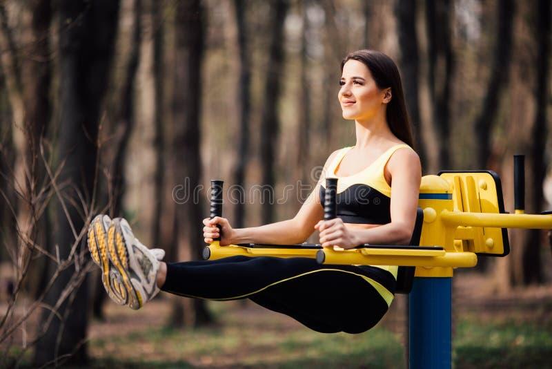 Mujer que ejercita con el equipo del ejercicio en el parque público Mujer en una formación en simulador de los deportes en el pat fotografía de archivo libre de regalías