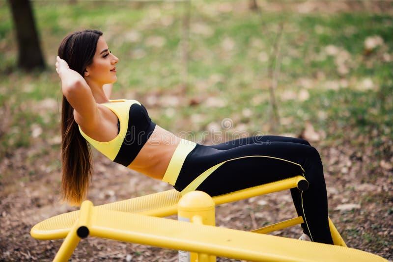 Mujer que ejercita con el equipo del ejercicio en el parque público Mujer en una formación en simulador de los deportes en el pat imagen de archivo