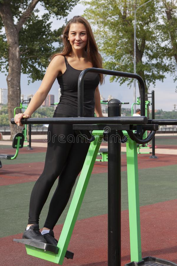 Mujer que ejercita con el equipo del ejercicio en el parque p?blico Mujer en una formaci?n en simulador de los deportes en el pat foto de archivo libre de regalías