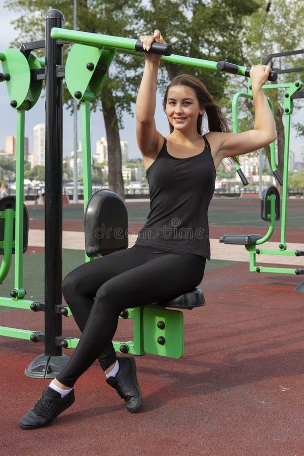 Mujer que ejercita con el equipo del ejercicio en el parque p?blico Mujer en una formaci?n en simulador de los deportes en el pat imagen de archivo