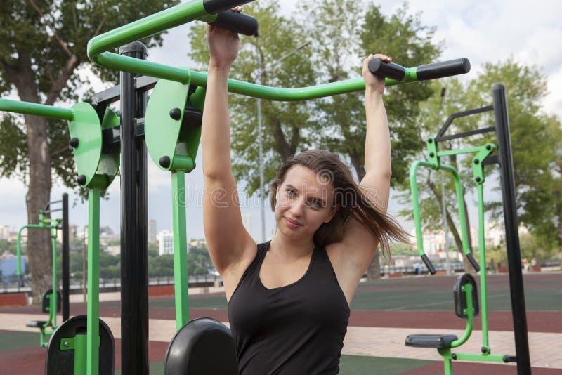 Mujer que ejercita con el equipo del ejercicio en el parque p?blico Mujer en una formaci?n en simulador de los deportes en el pat fotos de archivo libres de regalías