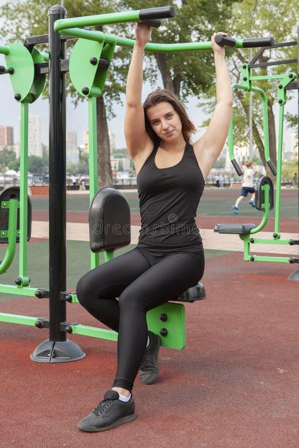 Mujer que ejercita con el equipo del ejercicio en el parque p?blico Mujer en una formaci?n en simulador de los deportes en el pat foto de archivo