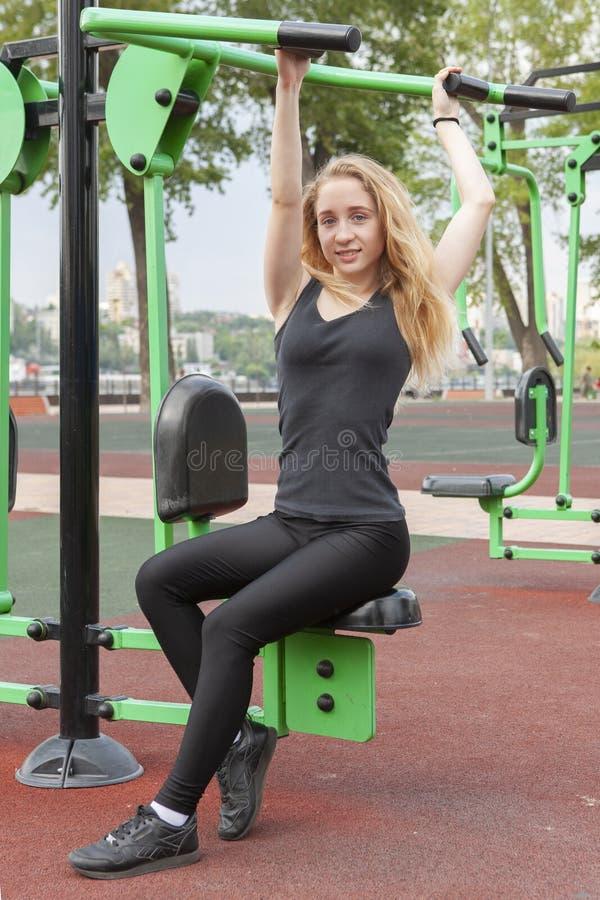 Mujer que ejercita con el equipo del ejercicio en el parque p?blico Mujer en una formaci?n en simulador de los deportes en el pat imagenes de archivo