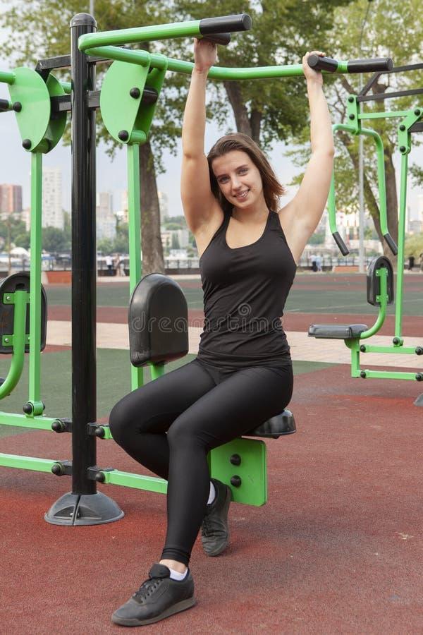 Mujer que ejercita con el equipo del ejercicio en el parque p?blico Mujer en una formaci?n en simulador de los deportes en el pat fotografía de archivo libre de regalías