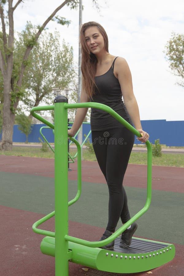 Mujer que ejercita con el equipo del ejercicio en el parque p?blico Mujer en una formaci?n en simulador de los deportes en el pat fotos de archivo