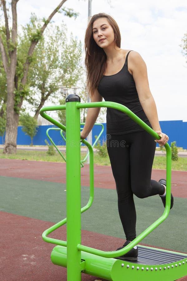 Mujer que ejercita con el equipo del ejercicio en el parque p?blico Mujer en una formaci?n en simulador de los deportes en el pat imagen de archivo libre de regalías