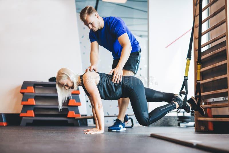 Mujer que ejercita con el instructor personal en el gimnasio imagen de archivo libre de regalías