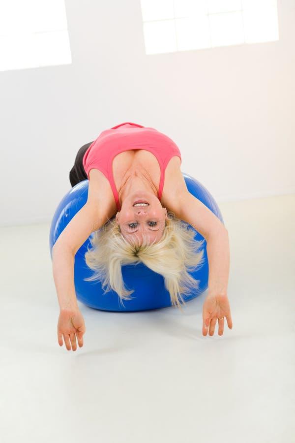 Mujer que ejercita con la bola de la aptitud fotos de archivo