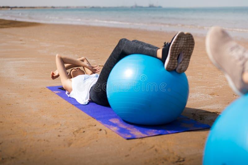 Mujer que ejercita con la bola de los pilates en la playa foto de archivo
