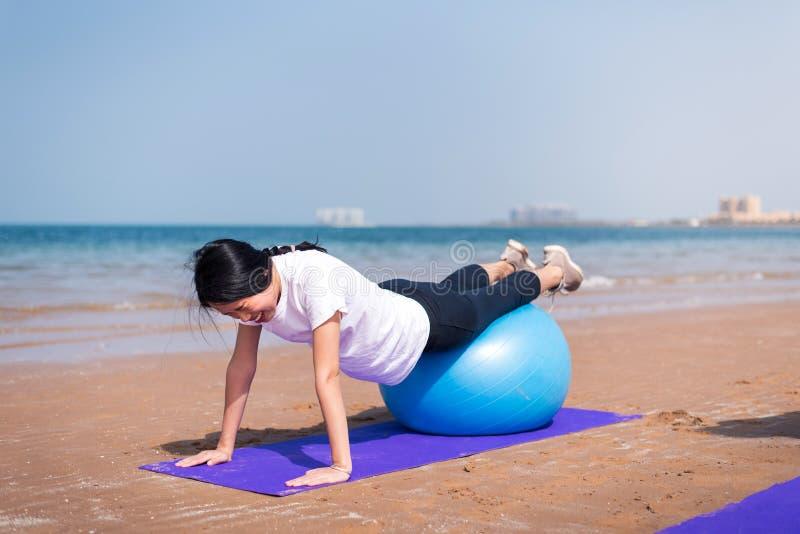 Mujer que ejercita con la bola de los pilates en la playa imagenes de archivo