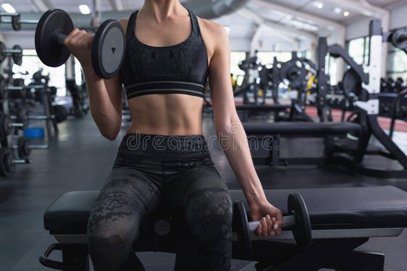 Mujer que ejercita con pesa de gimnasia en centro de aptitud fotos de archivo