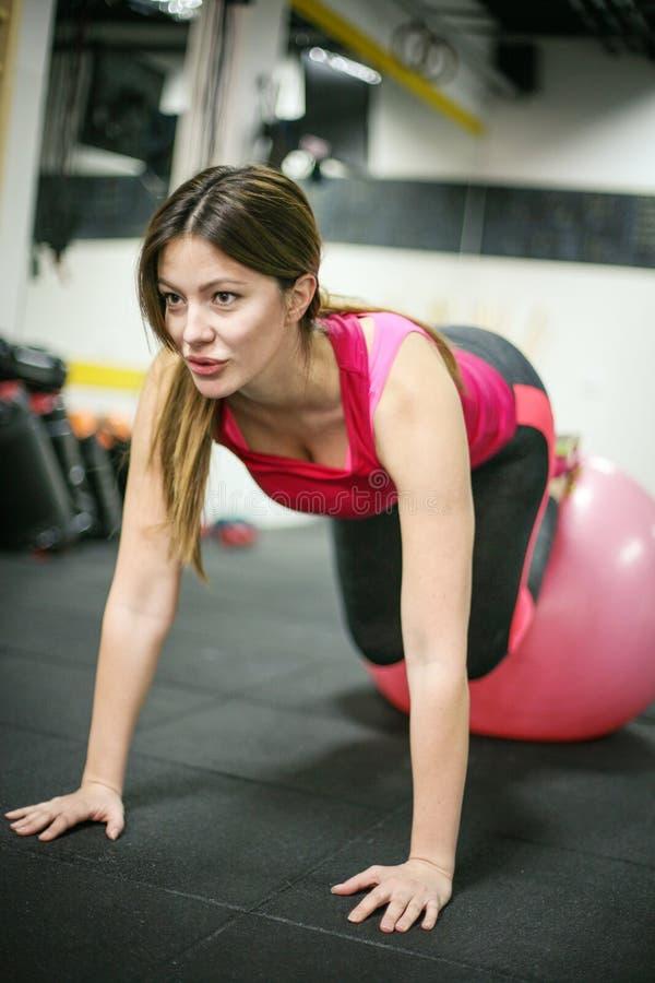 Mujer que ejercita con una bola del ajuste en gimnasio del vintage fotografía de archivo