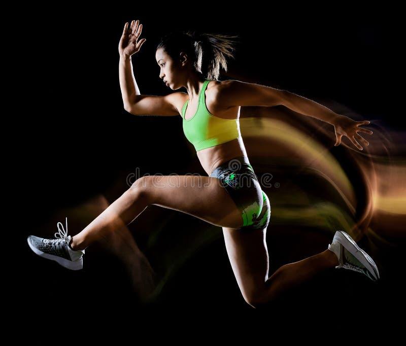 Mujer que ejercita efecto lightpainting aislado ejercicios del fondo negro de la aptitud foto de archivo libre de regalías