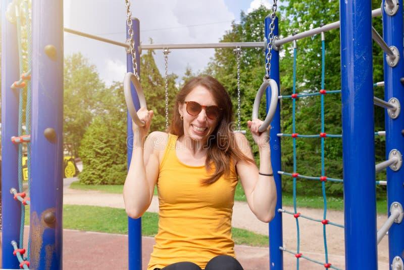 Mujer que ejercita en el patio por diversión Mujer que ejercita con los anillos gimn?sticos foto de archivo