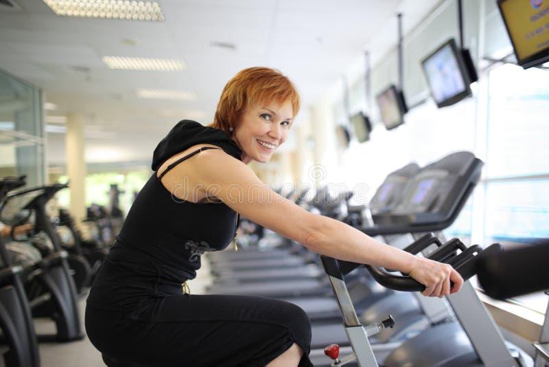 Mujer que ejercita en la bici foto de archivo