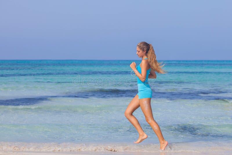 Mujer que ejercita en la costa de la playa imagenes de archivo