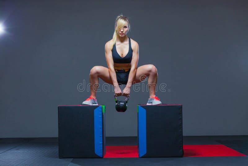 Mujer que ejercita en un gimnasio con un peso del kettlebell, en los cubos imágenes de archivo libres de regalías